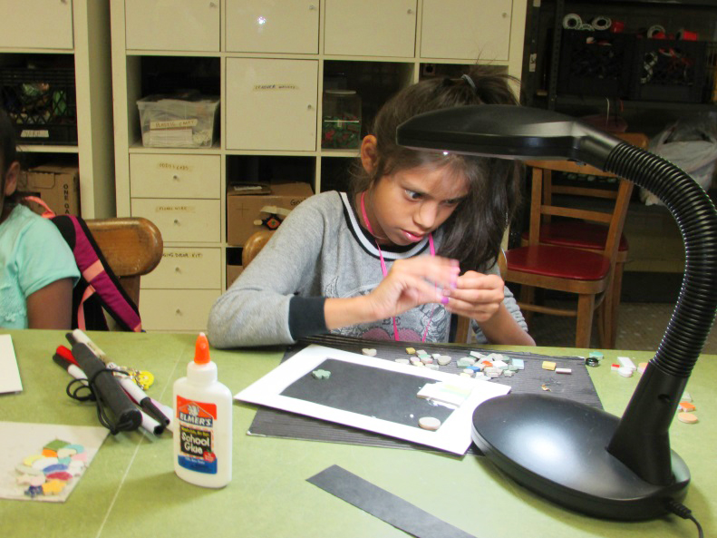 young girl gluing miscellaneous objects to black paper under bright table light