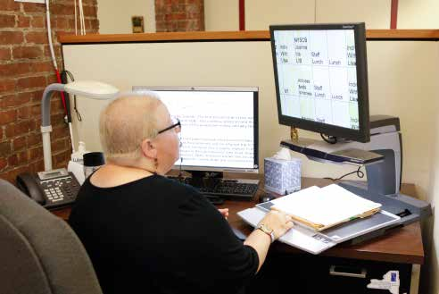 Lady working dual monitors on her small desk