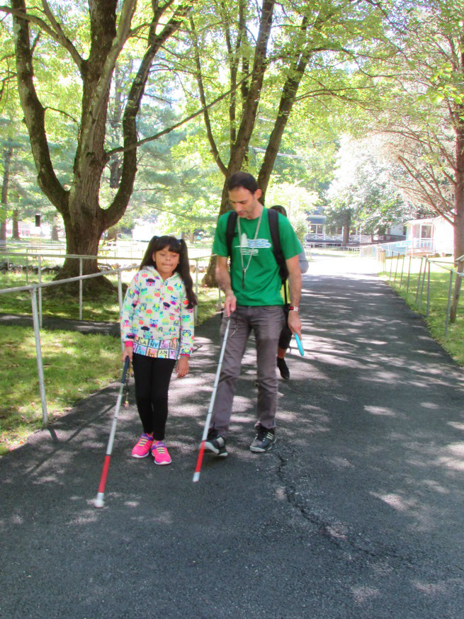 Man and girl walking in park with canes