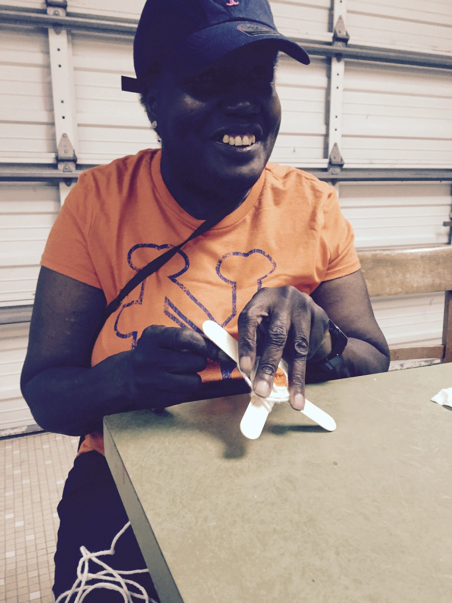 Senior Center - BS crafts - lady crafting a god's eye with yarn and tongue depressors