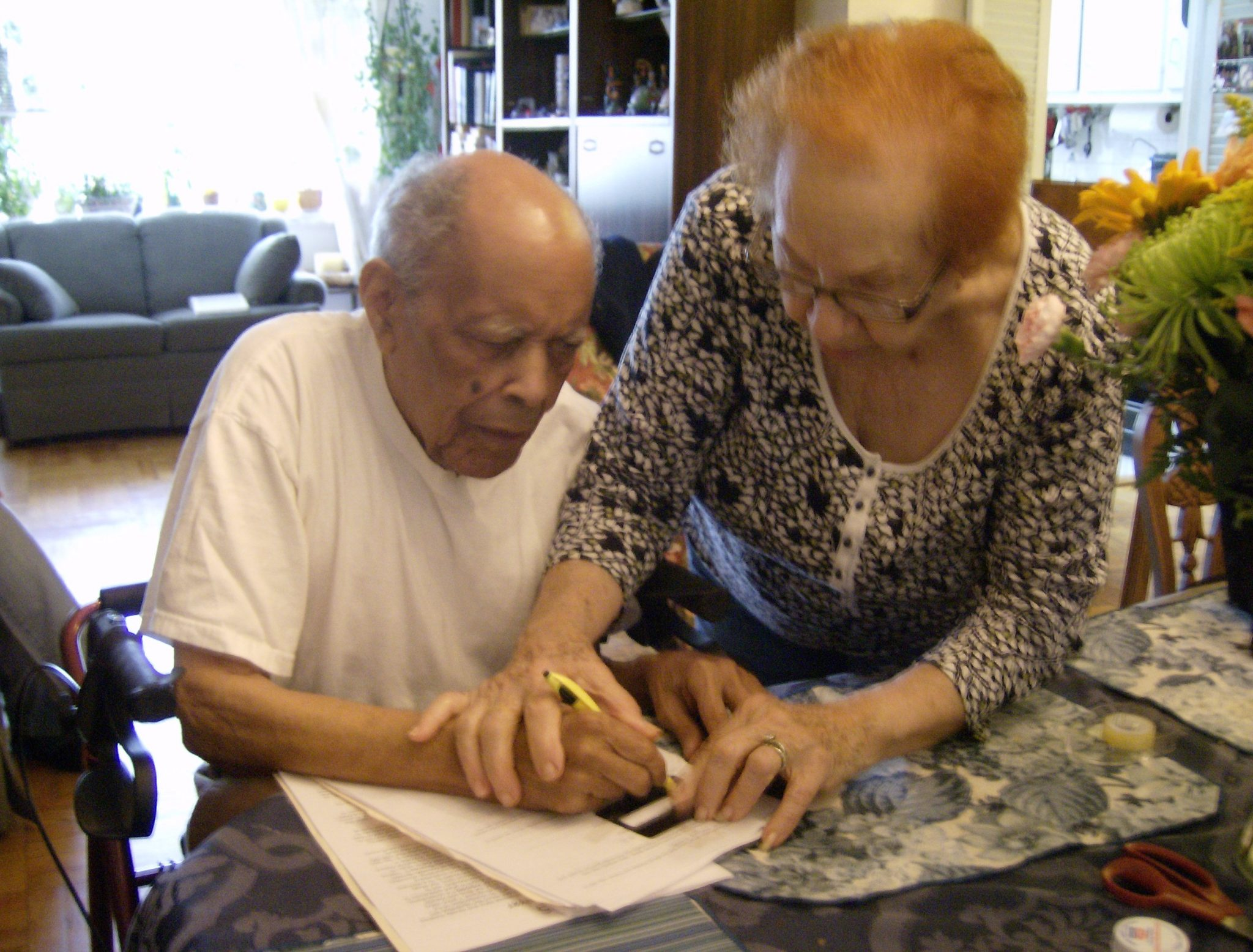 carmen and antonio- caregivers - Elderly woman (wife?) helping elderly man (husband?) write with pen and paper