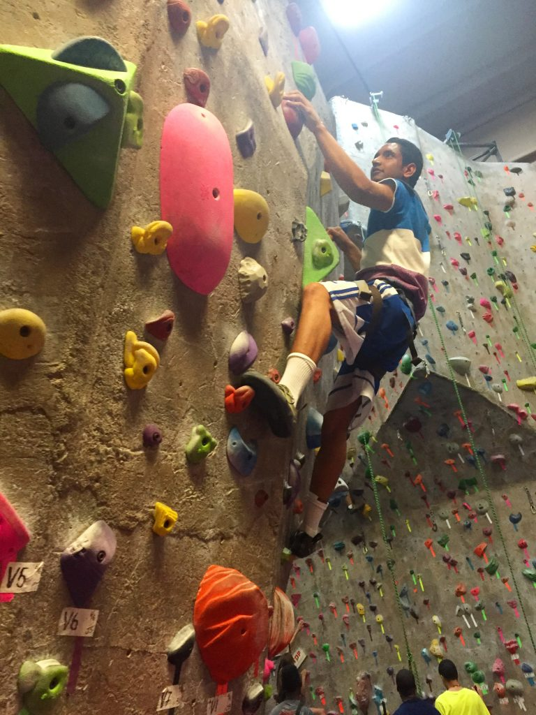 young man top roping a climbing wall