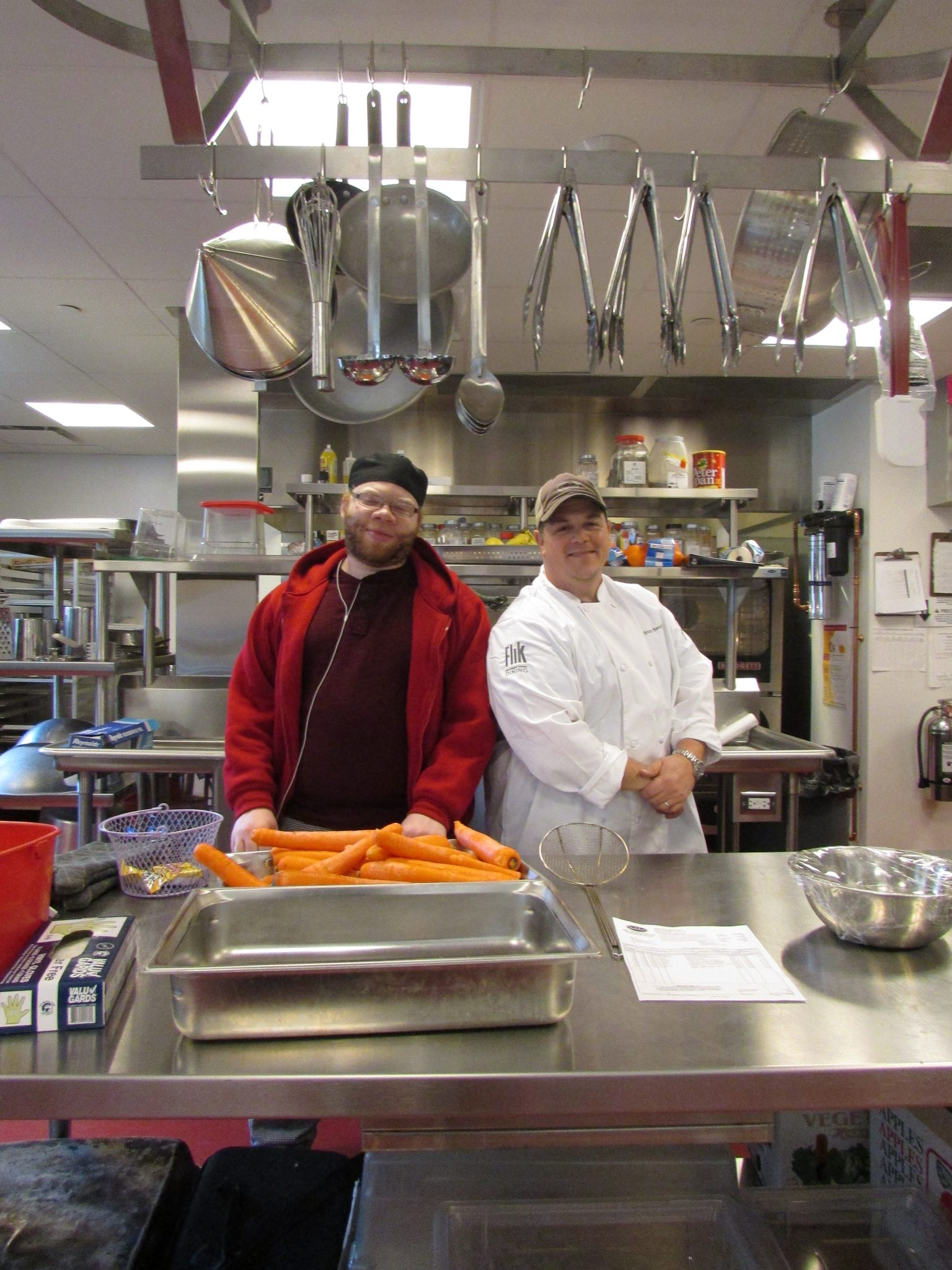 Image description: A man wearing a red sweater and black t-shirt stands next to a man wearing a chef's jacket in a large industrial kitchen. A tray of unchopped carrots sits in front of the men in a metal tray.