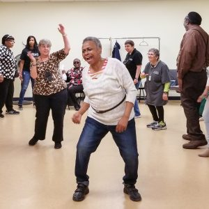 Image description: A smiling older woman dances in the middle of a room at VISIONS Center on Aging, surrounded by other older adults dancing.