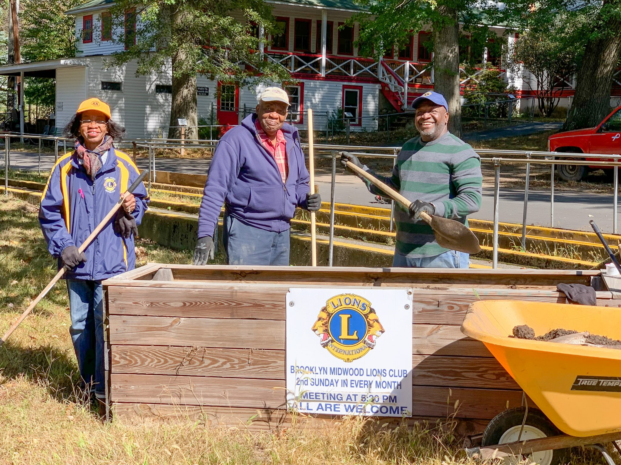 Three members of the Brooklyn Midwood Lions Club stand and smile to the camera while holding shovels.
