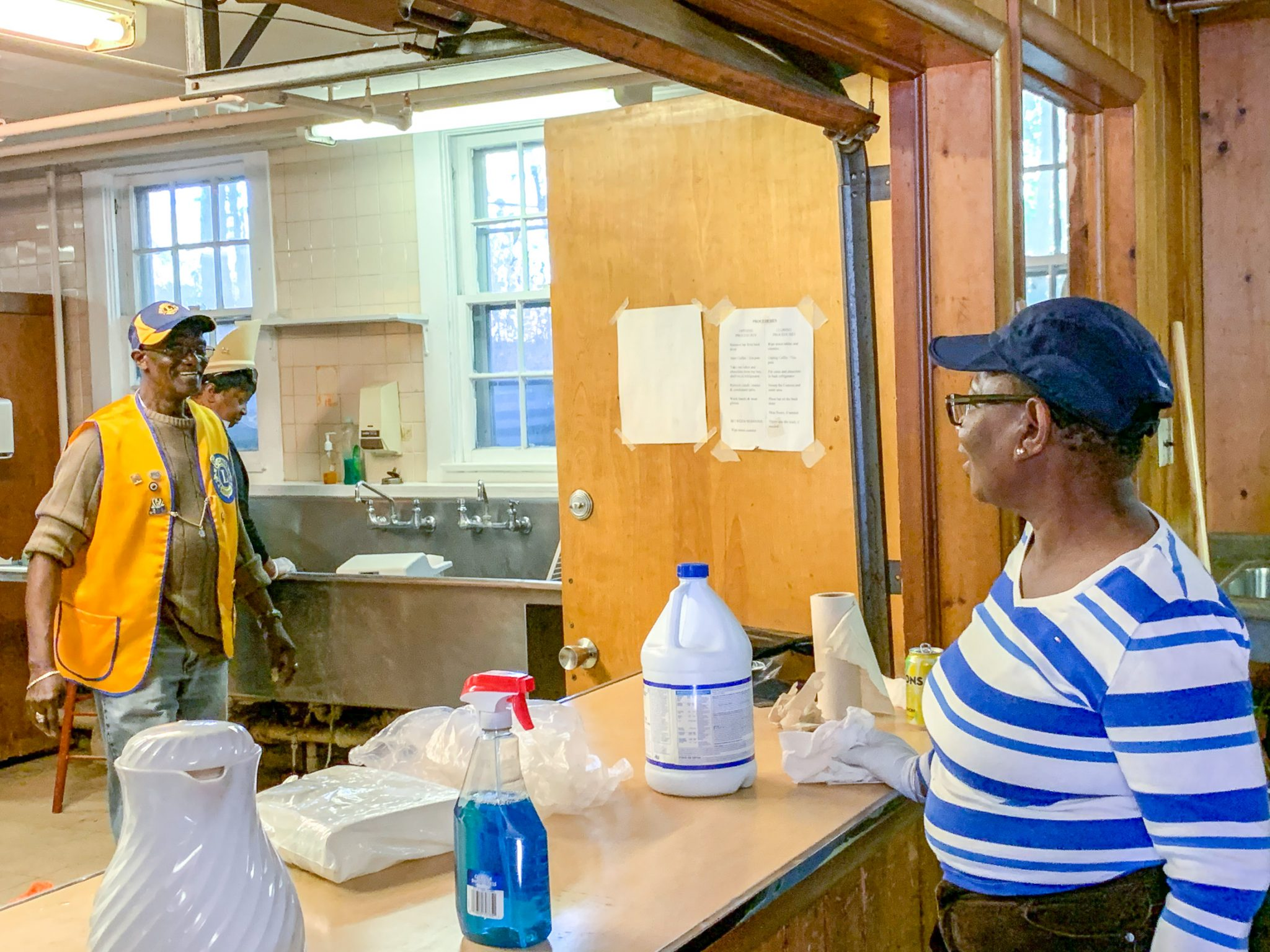 Two Lions Members stand in a kitchen inside VCB surrounded by cleaning products and tools.