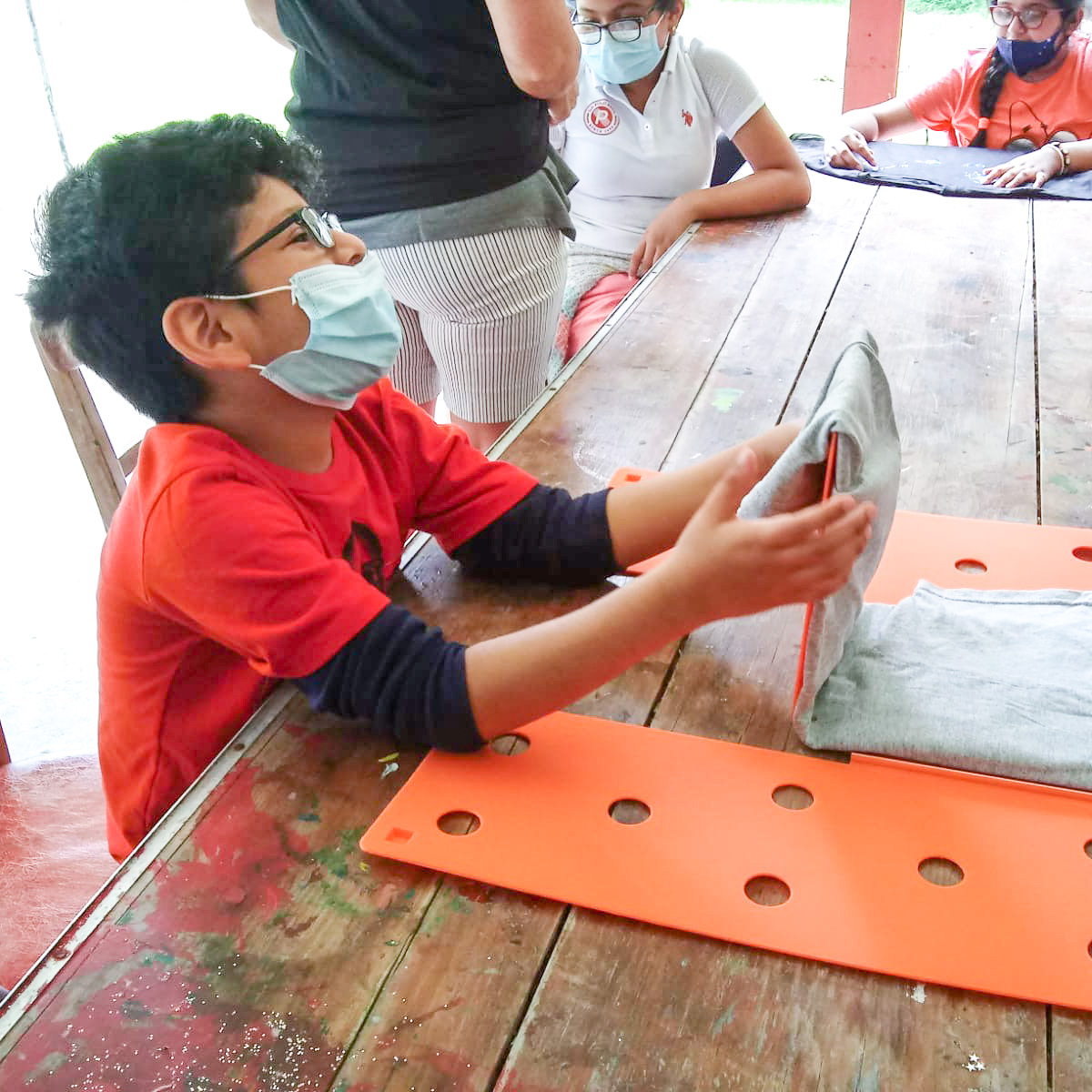 A young boy wearing a mask sits at a table and uses a shirt folding board to fold a gray t-shirt.