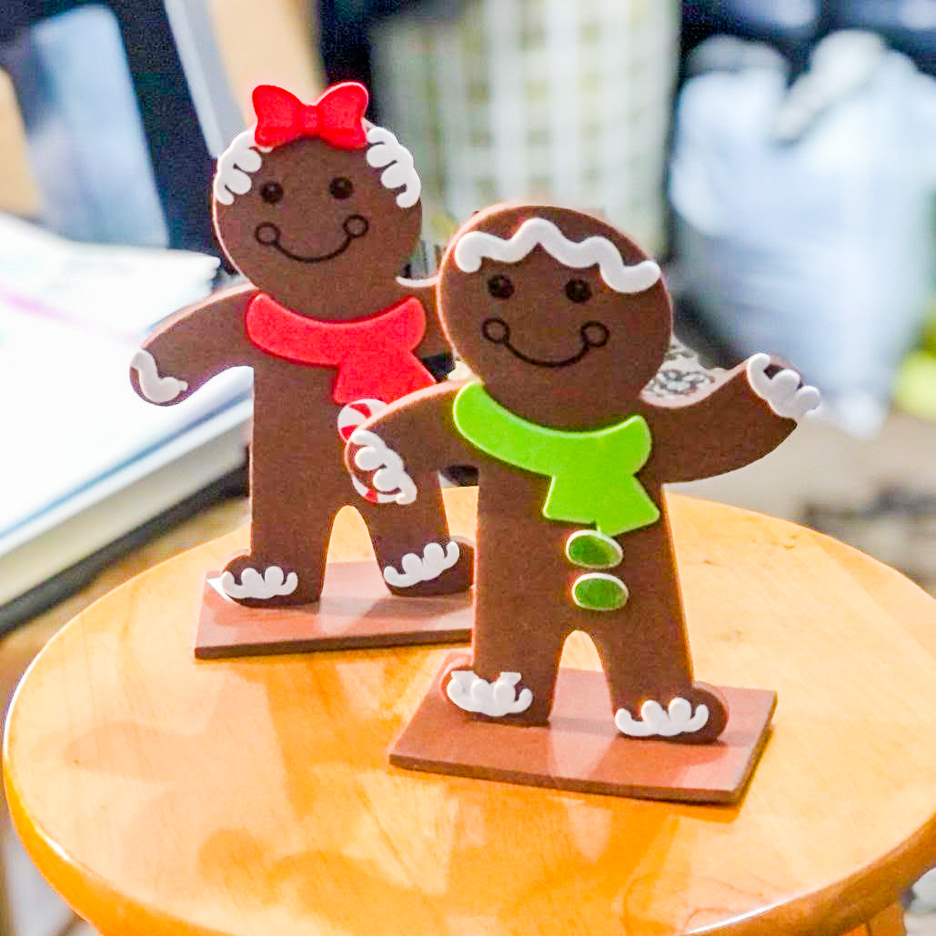 Two handcrafted gingerbread people wearing red and green scarves respectively, stand on a wooden table. The caption below reads, Photo of an older adult holiday virtual Arts & Crafts activity where participants made gingerbread people