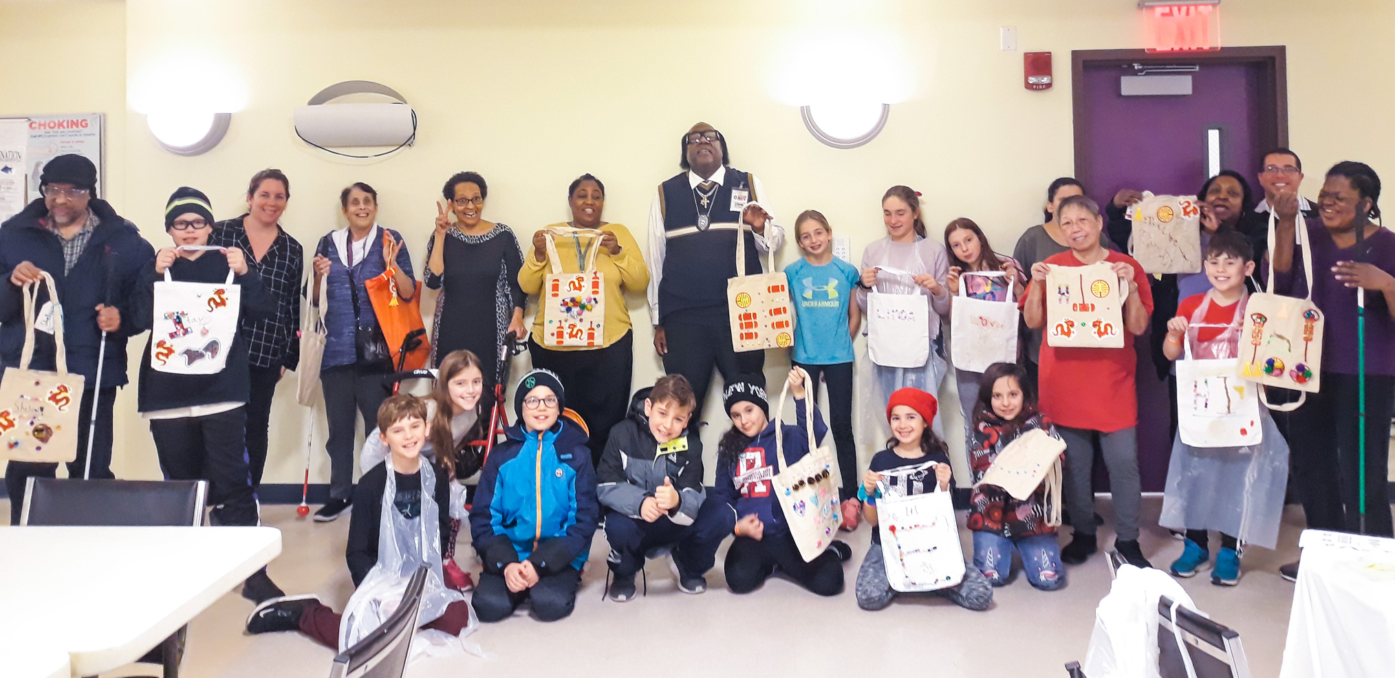 A group of students, older adults, and VISIONS staff stand together holding up tote bags they worked together to design.