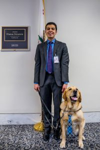 Laurel stands with his guide dog in a white office