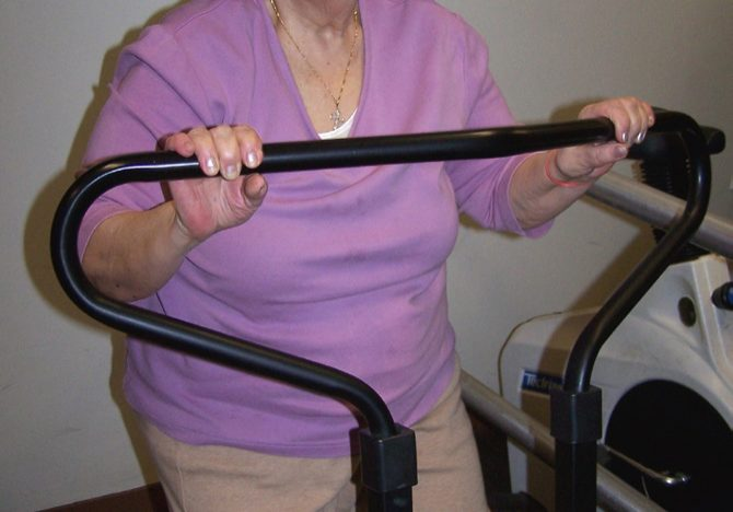 older lady in pink on old school workout equipment