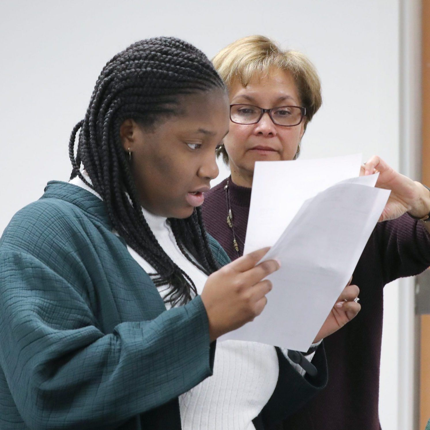 Image description: Two women in an office hold up and review paperwork.