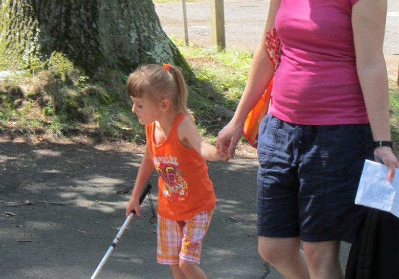 little girl learning how to walk with a can