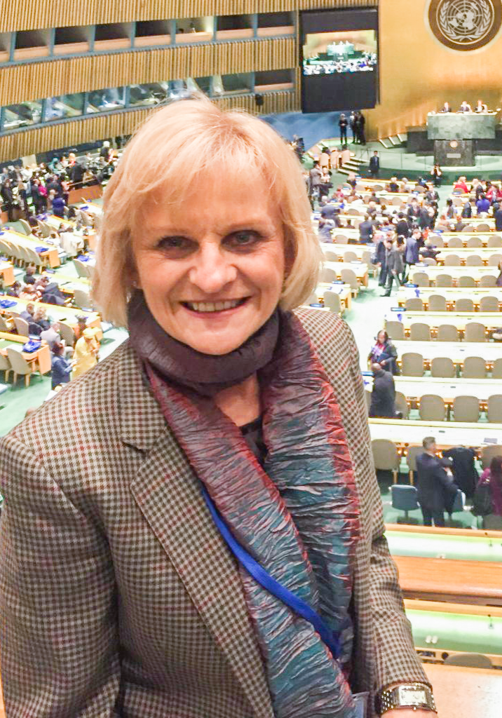 Headshot of VISIONS Board Member, Dr. Cynthia Stuen, a woman standing on a stage inside the United Nations.