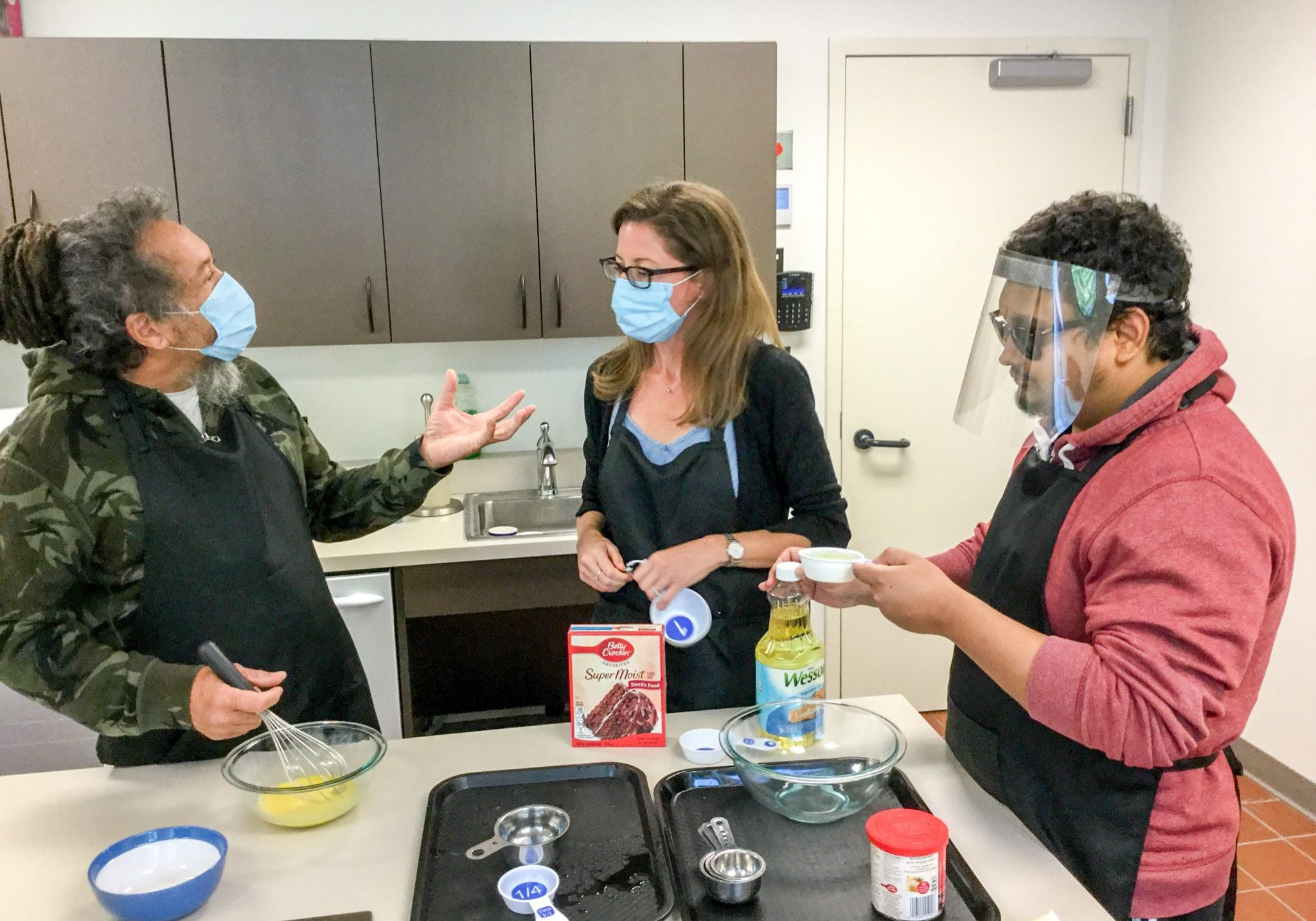 Two participants and an instructor all wearing masks stand in a kitchen and make brownies, utilizing adaptive kitchen tools.