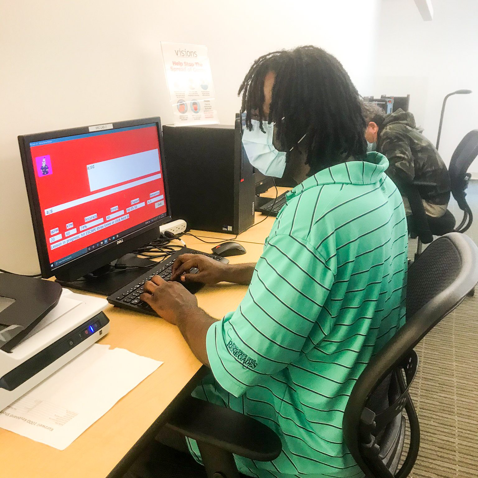 A young man wearing a mask, sitting in front of a computer at VISIONS Vocational Rehabilitation Center