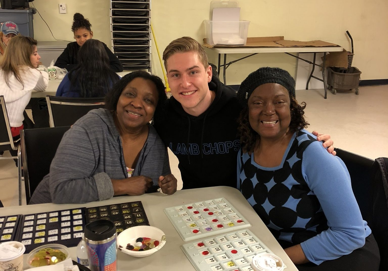 Michelle and Roz enjoying game night with a volunteer: three smiling faces at bingo!
