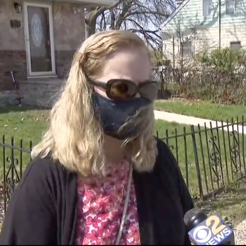 Image of VISIONS rehabilitation instructor, Tara Olsen, a woman standing outside a house wearing a mask and speaking into a CBS News microphone.