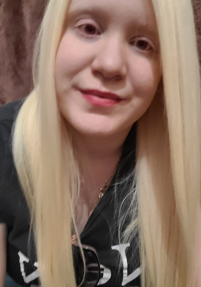 Headshot of Vanessa Luna, a woman with long blonde hair wearing a black t shirt, smiling to the camera